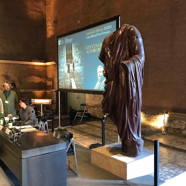 La statua di porfido rosso di Traiano nella Curia Iulia con alle spalle (illuminato) il basamento dell'altare della Vittoria